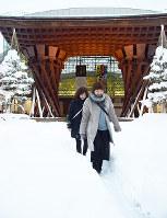 積もった雪の中にできた小道を歩く人たち=金沢市木ノ新保町のJR金沢駅東口で、久木田照子撮影