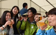 Participants are seen enjoying their drinks at a local beer tasting event at Baeren Brewery Co. Ltd. in Morioka, Iwate Prefecture, on May 6, 2017. (Mainichi)