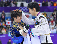 Men's figure skating gold medalist Yuzuru Hanyu, right, pats the head of teammate Shoma Uno, who took silver, during the ceremony after the free skating program at the Gangneung Ice Arena at the 2018 Winter Olympics in South Korea, on Feb. 17, 2018. (Mainichi)