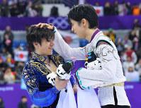 男子フリーの演技を終え、セレモニーで、銀メダルとなった宇野昌磨(左)の頭をなでる優勝した羽生結弦=江陵アイスアリーナで2018年2月17日、手塚耕一郎撮影