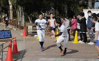 それぞれのチームでたすきをつなぐ長尾高校駅伝大会の参加者=大阪府枚方市の山田池公園で、岡崎英遠撮影
