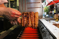 In this file photo, an eel filet is grilled during the high summer consumption period in Tokyo's Kita Ward, on July 25, 2017. (Mainichi)