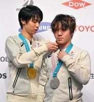 競技から一夜明け、記者会見で宇野昌磨の銀メダルのひもを直す、金メダルの羽生結弦=韓国・平昌で2018年2月18日午前10時47分、手塚耕一郎撮影