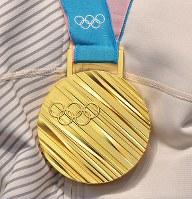 競技から一夜明け、記者会見で羽生結弦の胸にかけられた金メダル=韓国・平昌で2018年2月18日午前10時32分、手塚耕一郎撮影