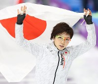 平昌五輪・女子1000メートルで銀メダルを獲得し、日の丸を手に客席からの声援に応える小平奈緒=江陵オーバルで2018年2月14日、佐々木順一撮影