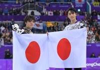 男子フリーの競技を終え、セレモニーで日の丸をかざす金メダルの羽生結弦(右)と、銀メダルの宇野昌磨=江陵アイスアリーナで2018年2月17日、手塚耕一郎撮影