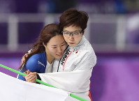 Japan's Nao Kodaira, right, and South Korea's Lee Sang-hwa hold each other after the women's 500 meters speed skating race at the Gangneung Oval at the 2018 Winter Olympics in Gangneung, South Korea, on Feb. 18, 2018. (Mainichi)