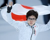 Japan's Nao Kodaira holds a national flag after she took first in the women's 500 meters speed skating event at the Gangneung Oval at the 2018 Winter Olympics in Gangneung, South Korea, on Feb. 18, 2018. (Mainichi)