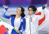 Japan's Nao Kodaira, right, and South Korea's Lee Sang-hwa wave to spectators after the women's 500 meters speed skating race at the Gangneung Oval at the 2018 Winter Olympics in Gangneung, South Korea, on Feb. 18, 2018. (Mainichi)