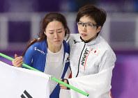 試合を滑り終え、抱き合う小平選手(右)と李選手