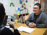 スタッフと話をする斉藤智文さん(右)=大阪市平野区で、玉木達也撮影