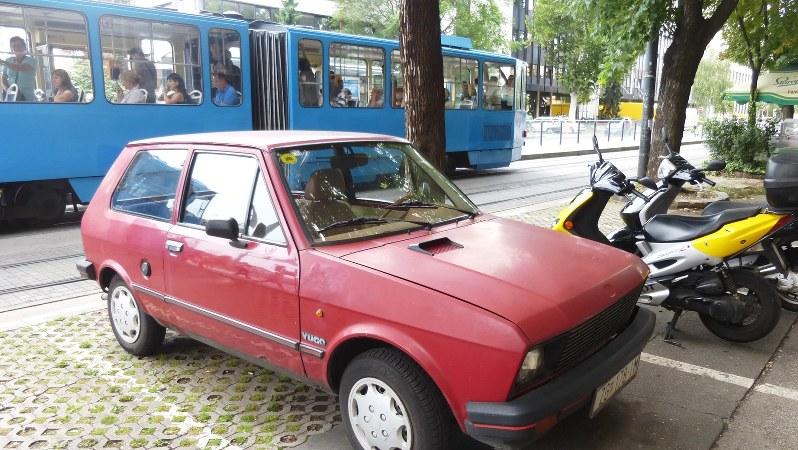 """旧ユーゴ時代を象徴する""""迷車""""「ユーゴ」。後ろの市電もたまたま旧型車(写真は筆者撮影)"""