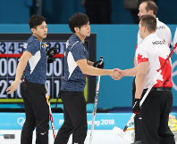 【日本―カナダ】第9エンドに1点を追加されてギブアップし、カナダの選手と握手する両角友佑(中央)。左は両角公佑=江陵カーリングセンターで2018年2月20日、佐々木順一撮影