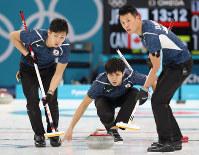 【日本―カナダ】第7エンド、ストーンを投じる両角友佑(中央)。右は山口剛史、左は両角公佑=江陵カーリングセンターで2018年2月20日、佐々木順一撮影
