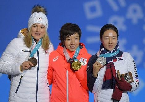 【平昌五輪】スピードスケート女子500メートルの表彰式で、金メダルを手に笑顔を見せる小平奈緒(中央)と、銀メダルの李相花(右)、銅メダルのエルバノバ=平昌メダルプラザで2018年2月20日、手塚耕一郎撮影