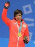 【平昌五輪】スピードスケート女子500メートルの表彰式で、金メダルを胸に笑顔で手を振る小平奈緒=平昌メダルプラザで2018年2月20日、手塚耕一郎撮影