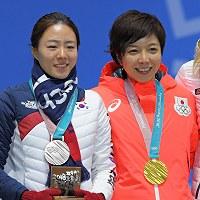 【平昌五輪】スピードスケート女子500メートルの表彰式で、金メダルを胸に笑顔を見せる小平奈緒(右)と、涙を流しながら並ぶ銀メダルの李相花=平昌メダルプラザで2018年2月20日、手塚耕一郎撮影