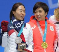 【平昌五輪】スピードスケート女子500メートルの表彰式で言葉を交わす、金メダルの小平奈緒(右)と、銀メダルの李相花=平昌メダルプラザで2018年2月20日、手塚耕一郎撮影