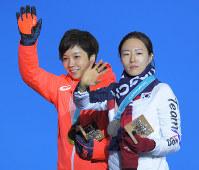 【平昌五輪】スピードスケート女子500メートルの表彰式を終え、並んで手を振って退場する、金メダルの小平奈緒(左)と、銀メダルの李相花=平昌メダルプラザで2018年2月20日、手塚耕一郎撮影