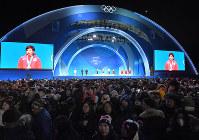 【平昌五輪】スピードスケート女子500メートルの表彰式え、金メダルの小平奈緒が大画面に映される中、国歌斉唱を聞く大勢の観客たち=平昌メダルプラザで2018年2月20日、手塚耕一郎撮影