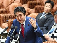 Prime Minister Shinzo Abe answers a question about flawed labor survey data as Health, Labor and Welfare Minister Katsunobu Kato, rear, looks on during a House of Representatives Budget Committee meeting on Feb. 20, 2018. (Mainichi)
