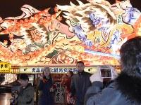 大型ねぶたの前で記念撮影をする中国人観光客ら青森市の「ねぶたの家ワ・ラッセ」で2018年2月19日午前、一宮俊介撮影