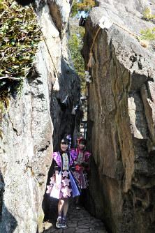 滋賀県東近江市の太郎坊宮の名所「夫婦岩」を通り抜ける佐々木さん(右)と高城さん=東近江市小脇町で2018年2月20日午後1時5分、金子裕次郎撮影