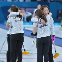 【スイスー日本】スイスにギブアップし、抱き合ってあいさつする日本選手たち。その後に米国が敗れ、日本の準決勝進出が決まった=江陵カーリングセンターで2018年2月21日、手塚耕一郎撮影