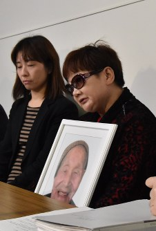 Mieko Okubo holds a photo of Fumio Okubo during a news conference at the Fukushima Prefectural Government headquarters on Feb. 20, 2018. (Mainichi)