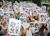 People protesting against security-related legislation hold up placards reading