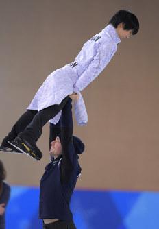 エキシビションに向けた練習の合間に、イタリアのペア選手にリフトされる羽生結弦(上)=江陵アイスアリーナで2018年2月22日、手塚耕一郎撮影