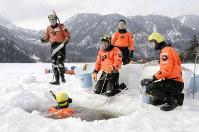 氷結した湯ノ湖で行われた海上保安庁特殊救難隊の潜水訓練=栃木県日光市の湯ノ湖で2018年2月21日、花野井誠撮影