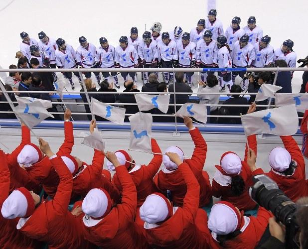 アイスホッケー女子の韓国、北朝鮮合同チーム「コリア」の選手たちに統一旗を振って声援を送る北朝鮮の応援団(手前)=2018年2月10日、手塚耕一郎撮影