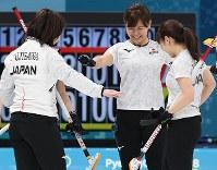【日本―韓国】第9エンド、3点差から1点差まで詰め寄り、野球の審判の「セーフ」のポーズを取る吉田知那美(右奥)ら日本の選手たち=江陵カーリングセンターで2018年2月23日、宮間俊樹撮影