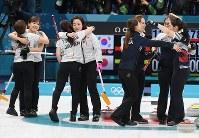 【日本―韓国】延長第11エンドの末、韓国に敗れて抱き合う日本代表の選手たち(左)。右は決勝進出を決めて喜ぶ韓国の選手たち=江陵カーリングセンターで2018年2月23日、宮間俊樹撮影