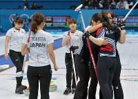 【日本―韓国】延長第11エンド、最後のストーンで韓国が勝利を決め、抱き合う韓国選手たち(右)を横目に、険しい表情を見せる日本選手ら=江陵カーリングセンターで2018年2月23日、手塚耕一郎撮影