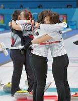 【日本―韓国】延長第11エンド、最後のストーンで韓国が勝利を決め、負けて抱き合う日本選手(手前)と、決勝進出を決めて抱き合う韓国選手ら=江陵カーリングセンターで2018年2月23日、手塚耕一郎撮影