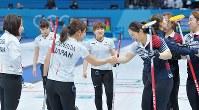 【日本―韓国】延長第11エンド、最後のストーンで韓国が勝利を決め、硬い表情で韓国選手と握手を交わす日本選手たち(左)=江陵カーリングセンターで2018年2月23日、手塚耕一郎撮影