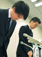 記者会見で謝罪するコインチェックの和田晃一良社長(左)と大塚雄介取締役=東京都中央区で2018年1月26日午後11時37分、手塚耕一郎撮影
