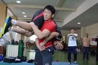 ロンドン五輪のレスロングで金メダルを獲得した米満達弘に抱え上げられる吉田圭伸=自衛隊体育学校で2013年5月9日、江連能弘撮影