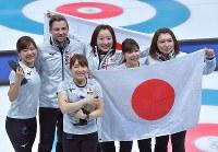 【日本-英国】銅メダルを獲得し、日の丸を手に笑顔を見せる藤沢五月(中央)ら日本の選手とリンドコーチ(左から2人目)=江陵カーリングセンターで2018年2月24日、手塚耕一郎撮影
