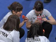 第5エンドを終え、休憩タイムにかなり大きなイチゴを手にする吉田知那美(左奥)と日本チームの選手たち=江陵カーリングセンターで2018年2月24日、手塚耕一郎撮影