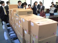 Opposition lawmakers, pictured at rear, ask questions about the 32 boxes of survey forms at the Ministry of Health, Labor and Welfare in Tokyo's Chiyoda Ward on Feb. 23, 2018. (Mainichi)