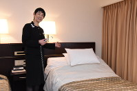 「バーズアイ」を率いる客室支配人の中村さおりさん。ユニバーサルルームのベッドは傾きを調節することができ、体を起こしやすい=京王プラザホテルで