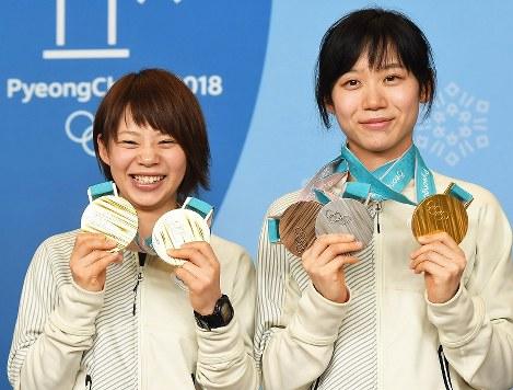 メダルを手に、記者会見で記念撮影に応じる高木菜那(左)と高木美帆=平昌のメインプレスセンターで2018年2月25日、山崎一輝撮影