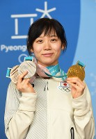 メダルを手に、記者会見で記念撮影に応じる高木美帆=平昌のメインプレスセンターで2018年2月25日、山崎一輝撮影