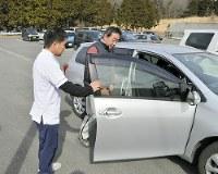 実車訓練のため自前の運転コースに向かう山崎清隆さん(右)と作業療法士の那須識徳さん=静岡県伊豆市の農協共済中伊豆リハビリテーションセンターで