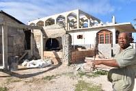 壁が崩壊したままの自宅を指さすセルスティーノ・ドゥアルさん。奥は、人を雇って再建が進むドイツ人宅=ハバナで2018年2月1日