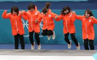 Japan's bronze-medal winning women's curling team jumps onto the podium during the ceremony in Gangneung, South Korea, on Feb. 25, 2018. (Mainchi)