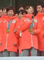 帰国報告会でインタビューを受ける高木菜那(右)の後ろでスケートのポーズをとる高木美帆(前列中央)=東京都港区で2018年2月27日午前11時3分、藤井達也撮影